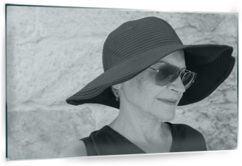 Panel szklany do kuchni - Head and shoulders view of beautiful older woman in hat and sunglasses against stone wall (black and white)