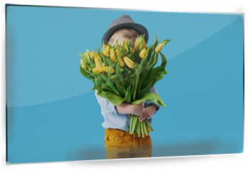 Panel szklany do kuchni - Cute smiling child holding a beautiful bouquet of yellow tulips in front of his face isolated on blue. Little toddler boy gives a bouquet to mom
