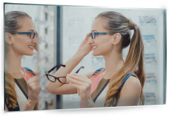 Panel szklany do kuchni - Young woman in optometrists store checking her looks in mirror