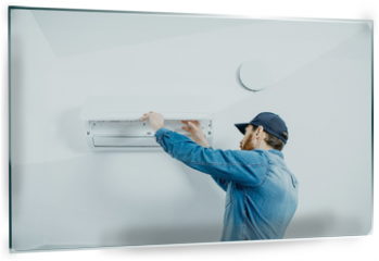 Panel szklany do kuchni - Repairman in blue workwear serving the air conditioner changing filter on the white wall background