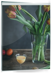 Panel szklany do kuchni - Colorful Easter eggs in nest, glass of egg nog and tulips in vase on wooden table.